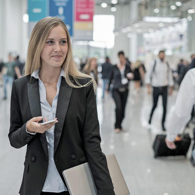 junge Frau auf einer Job-Messe hält Smartphone in der Hand