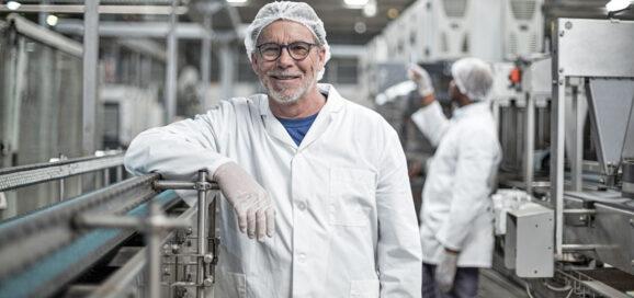 Ein Mann lehnt lächelnd an einer Produktionsanlage