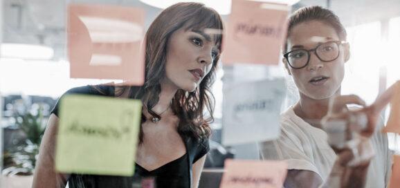 Zwei Frauen stehen vor einer Glaswand mit Post Its