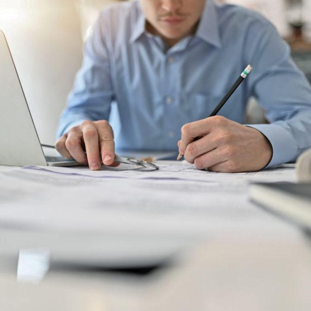 Mann am Schreibtisch vor einem Laptop notiert
