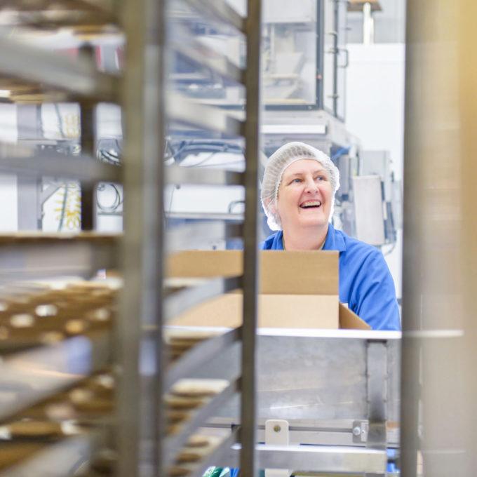Eine lachende, ältere Frau in einer Lebensmittel-Fabrik