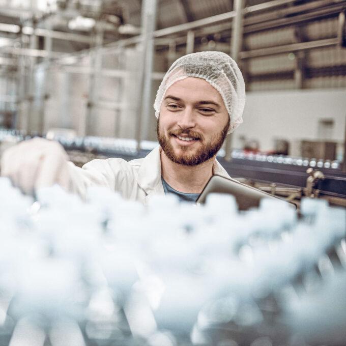 Ein junger Mann mit Haarnetz in einer Fabrik