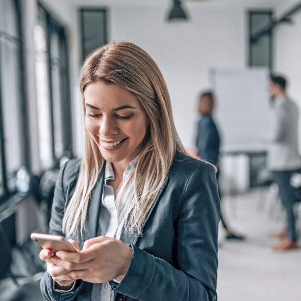 Eine junge Frau tippt etwas in ihr Smartphone ein und lächelt