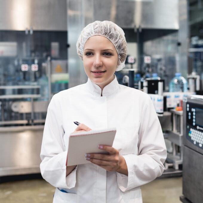 Eine junge Mitarbeiterin mit Kittel und Haarnetz notiert etwas auf einem Klemmbrett