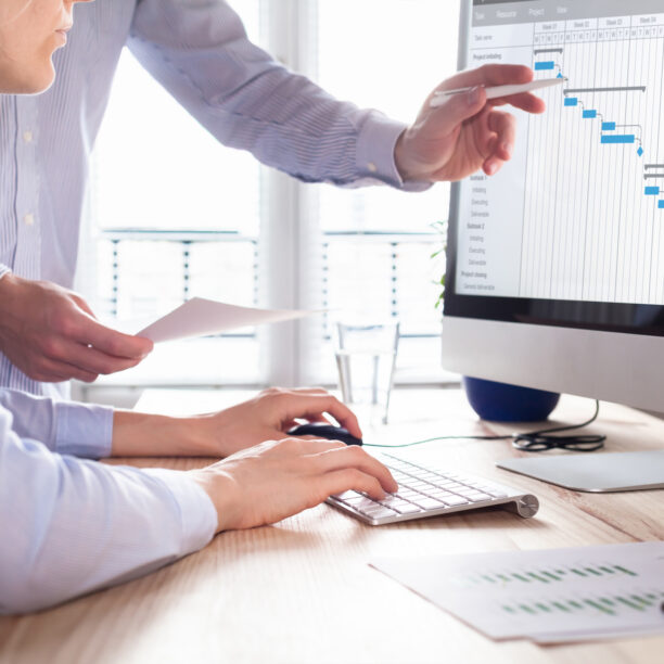Frau tippt auf Tatstatur und schaut zu Monitor während männliche Hand mit Stift auf Monitor zeigt
