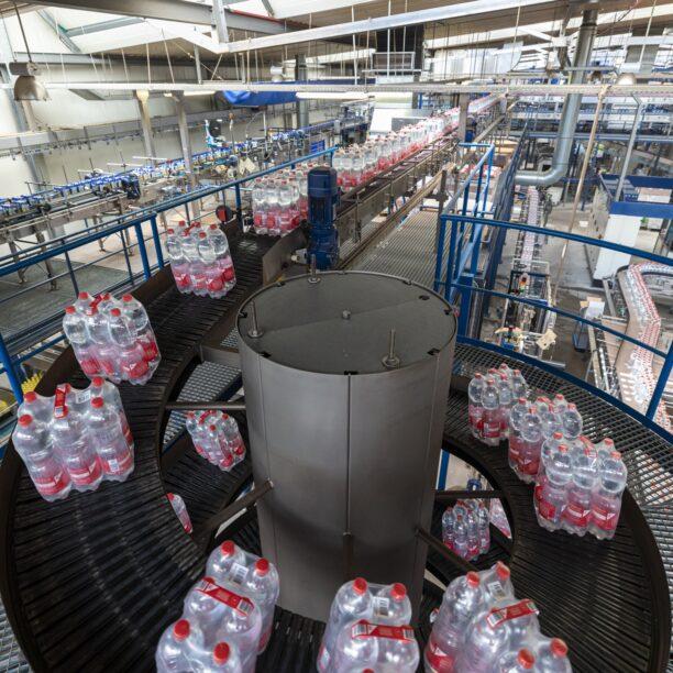 Sechser-Packs von Wasser werden über ein Förderband befördert