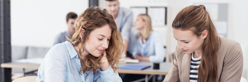 Zwei junge Mitarbeiterinnen sitzen über Formulare gebeugt