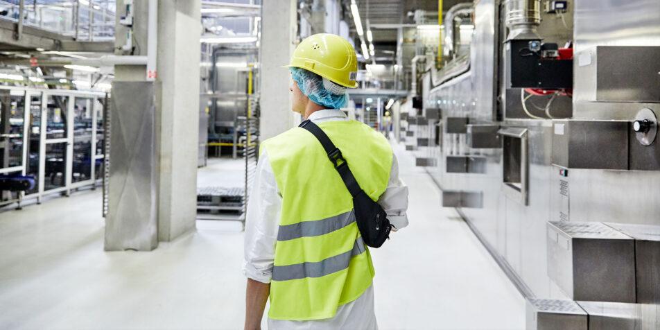 Ein Mitarbeiter mit Schutz-Kleidung in einer Produktionshalle
