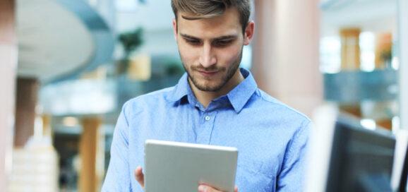Ein junger Mitarbeiter arbeitet am Tablet