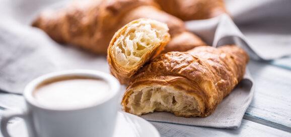 Eine Kaffee-Tasse und Croissants