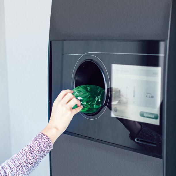Eine Flasche wird an einen Pfand-Automaten zurückgegeben